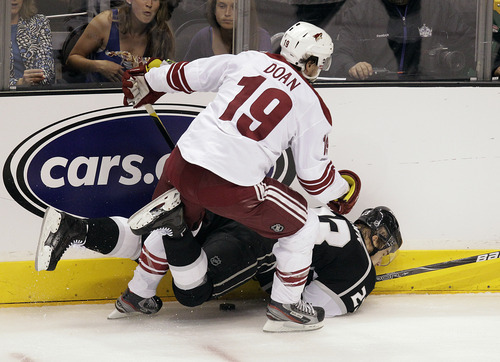 Los Angeles Kings right wing Dustin Brown, bottom, is checked by Phoenix Coyotes right wing Shane Doan during the first period of Game 4 of the NHL hockey Stanley Cup Western Conference finals in Los Angeles, Sunday, May 20, 2012. (AP Photo/Jae C. Hong)