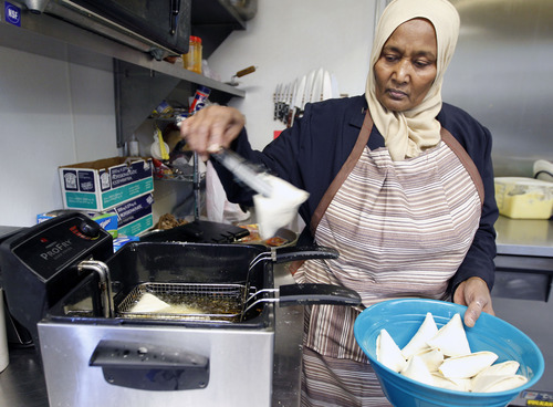 Al Hartmann  |  The Salt Lake Tribune Muna Ali, a Sudanese refugee, drops triangles of dough-wrapped meat and vegetables into oil this week. The sambousas were part of the lunch she was catering for a Utah Department of Health event.