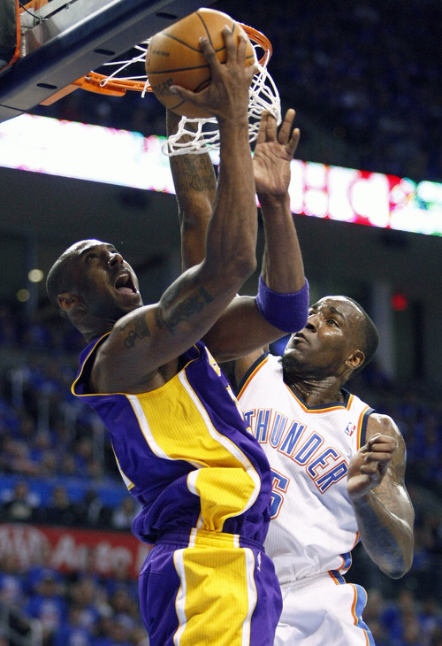 Los Angeles Lakers guard Kobe Bryant, left, goes up for a basket in front of Oklahoma City Thunder center Kendrick Perkins, right, during the first quarter of Game 5 in their NBA basketball Western Conference semifinal playoff series, Monday, May 21, 2012, in Oklahoma City. (AP Photo/Alonzo Adams)