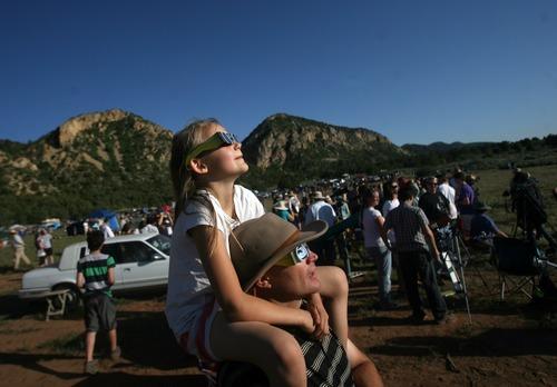 Kim Raff | The Salt Lake Tribune (top) Marissa, (bottom) Jon Wikan watch the annular solar eclipse at the public viewing area in Kanarraville, Utah on May 20, 2012.