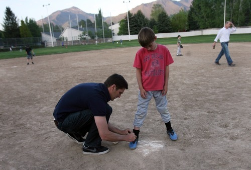 Kim Raff | The Salt Lake Tribune Josh Romney pauses to tie son Wyatt's, shoes during baseball practice at an LDS stake house in Holladay, Utah on May 3, 2012.