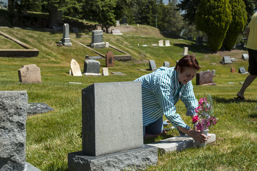 Chris Detrick  |  The Salt Lake Tribune Liz Shafer Zentner places flowers at the grave site of her great-grandfather Thoedore Marx at Salt Lake City Cemetery Saturday May 19, 2012.  The Shafer family visits the grave sites of family members every year to place flowers.
