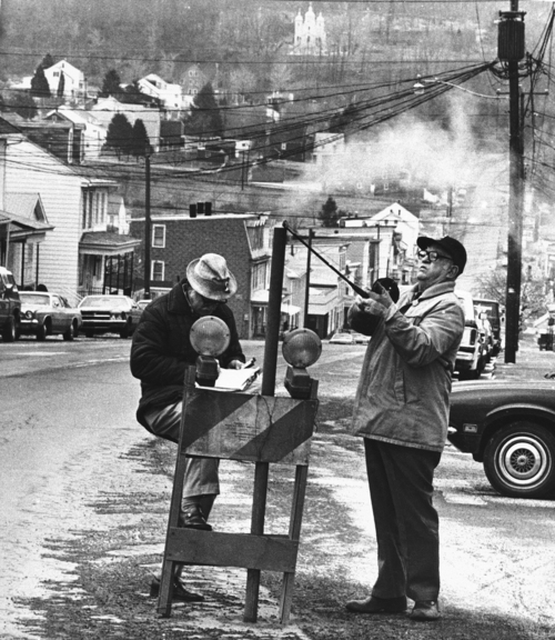 Paul Vathis | The Associated Press In April 1981, U.S. Bureau of Mines' John Stockalis, right, and Dan Lewis drop a thermometer through a hole on Main Street in Centralia, Pa., to measure the heat from a mine blaze that burns under the town. Fifty years ago on May 27 a fire at the town dump spread to a network of coal mines underneath hundreds of homes and business in the northeastern Pennsylvania borough of Centralia, eventually forcing the demolition of nearly every building.