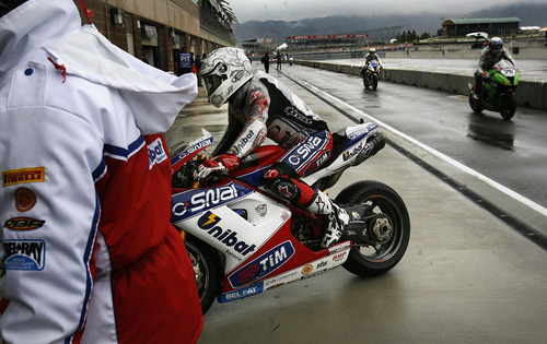 Scott Sommerdorf  |  The Salt Lake Tribune              Carlos Checa is escorted to his pit by a crew member after coming in from an FIM Superbike World Championship free practice on the wet track at Miller Motorsports Park, Saturday, May 26, 2012.