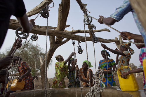 In this Tuesday, May 1, 2012 photo, women crowd a well in the village of Kiral, near Goudoude Diobe in the Matam region of northeastern Senegal. Wells in the area are often 75-meters deep, and aren't always able to produce enough water for residents' daily needs. Since late 2011, aid groups have been sounding the alarm, warning that devastating drought has again weakened communities where children already live perilously close to the edge of malnutrition. The situation is most severe in Niger, Chad and in Mali, but this time it has also pervaded northern Senegal, the most prosperous and stable country in the Sahel. (AP Photo/Rebecca Blackwell)
