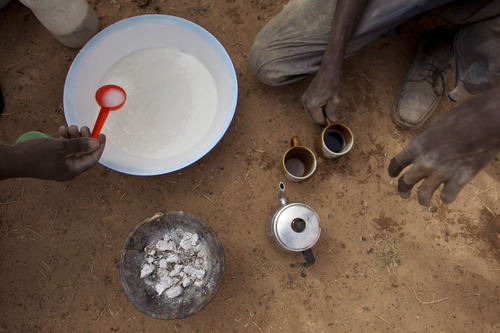 In this Tuesday, May 1, 2012 photo, men share a meager breakfast of thin porridge and instant coffee, during a break in building a mud-brick house for a neighbor, in the village of Goudoude Diobe, in the Matam region of northeastern Senegal. With little paid work available, a group of village men, including professional masons, have banded together to build houses for free for several residents. Since late 2011, aid groups have been sounding the alarm, warning that devastating drought has again weakened communities where children already live perilously close to the edge of malnutrition. The situation is most severe in Niger, Chad and in Mali, but this time it has also pervaded northern Senegal, the most prosperous and stable country in the Sahel. (AP Photo/Rebecca Blackwell)