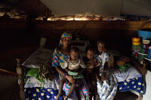 In this Monday, April 30, 2012 photo, Faty Ba and three of her five children, sit for a photograph in their hut in the village of Fass, in the Matam region of northeastern Senegal. Since late 2011, aid groups have been sounding the alarm, warning that devastating drought has again weakened communities where children already live perilously close to the edge of malnutrition.The situation is most severe in Niger, Chad and in Mali, but this time it has also pervaded northern Senegal, the most prosperous and stable country in the Sahel. (AP Photo/Rebecca Blackwell)