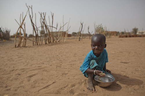 In this Tuesday, May 1, 2012 photo, 2-year-old Aliou Seyni Diallo eats dry couscous given to him by a neighbor, after he collapsed in tears of hunger in the village of Goudoude Diobe, in the Matam region of northeastern Senegal. Since late 2011, aid groups have been sounding the alarm, warning that devastating drought has again weakened communities where children already live perilously close to the edge of malnutrition. The situation is most severe in Niger, Chad and in Mali, but this time it has also pervaded northern Senegal, the most prosperous and stable country in the Sahel. (AP Photo/Rebecca Blackwell)