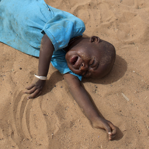In this Tuesday, May 1, 2012 photo, 2-year-old Aliou Seyni Diallo collapses in tears after not eating since the day before, in the village of Goudoude Diobe, in the Matam region of northeastern Senegal. A neighbor stepped in to help Aliou's struggling mother, giving the boy a bowl of dry couscous to stop his tears. Since late 2011, aid groups have been sounding the alarm, warning that devastating drought has again weakened communities where children already live perilously close to the edge of malnutrition.The situation is most severe in Niger, Chad and in Mali, but this time it has also pervaded northern Senegal, the most prosperous and stable country in the Sahel. (AP Photo/Rebecca Blackwell)