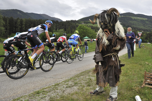 Cyclists pedal by a supporter with a weird costume during the 16th stage of the Giro d'Italia, Tour of Italy cycling race, from Limone sul Garda to Falzes - Pfalzen, Italy, Tuesday, May 22, 2012.  (AP Photo/Daniele Badolato)