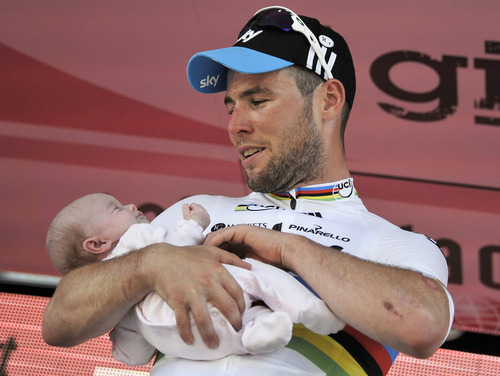 Britain's Mark Cavendish holds her daughter Delilah Grace as he celebrates on the podium after winning the fifth stage of the Giro d'Italia, Tour of Italy cycling race, from Modena to Fano, Italy, Thursday, May 10, 2012. World Champion Mark Cavendish won the fifth stage of the Giro d'Italia on Thursday, but there was more bad luck for Taylor Phinney as the American was caught up in another crash on the 199-kilometer leg from Modena to Fano. (AP Photo/Gian Mattia D'Alberto)