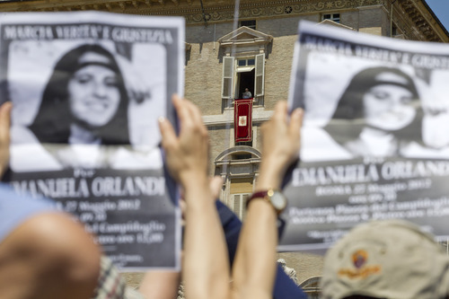 Demonstrators hold pictures of Emanuela Orlandi, as Pope Benedict XVI, background center, reads his message during the Regina Coeli noon prayer in St. Peter's square, at the Vatican, Sunday, May 27, 2012. Fifteen-year-old Emanuela Orlandi, the daughter of a Vatican messenger who lived with his family in Vatican City, disappeared 25 years ago (June 22, 1983) when she went to a music lesson. (AP Photo/Andrew Medichini)