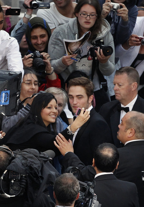 Actor Robert Pattinson, center right, greets fans as he arrives for the screening of Cosmopolis at the 65th international film festival, in Cannes, southern France, Friday, May 25, 2012. (AP Photo/Vincent Kessler, Pool)