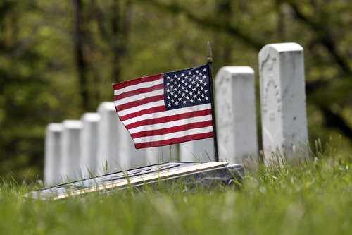 In this April 27, 2012 photo, a flag and marker are with grave stones for soldiers who died in action or after the Civil War at Albany Rural Cemetery in Menands, N.Y. Nearly 150 years after the last fusillade of the Civil War, historians, authors and museum curators are still finding new topics to explore as the nation commemorates the sesquicentennial of America's bloodiest conflict. Even the long-accepted death toll of 620,000, cited by historians since 1900, is being reconsidered. In a study published late last year in Civil War History, Binghamton University history demographics professor J. David Hacker said the toll is actually closer to 750,000. (AP Photo/Mike Groll)
