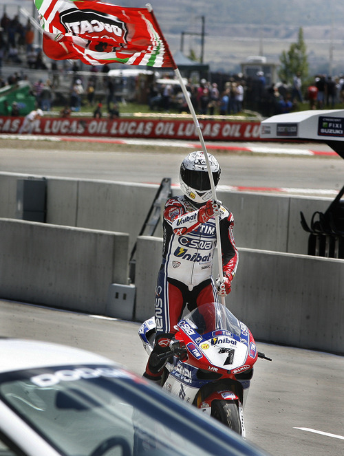Scott Sommerdorf     The Salt Lake Tribune              Carlos Checa stands up as he rides into the winners area holding a Ducati flag after winning FIM Superbike World Championship Race One, Monday, May 28, 2012.