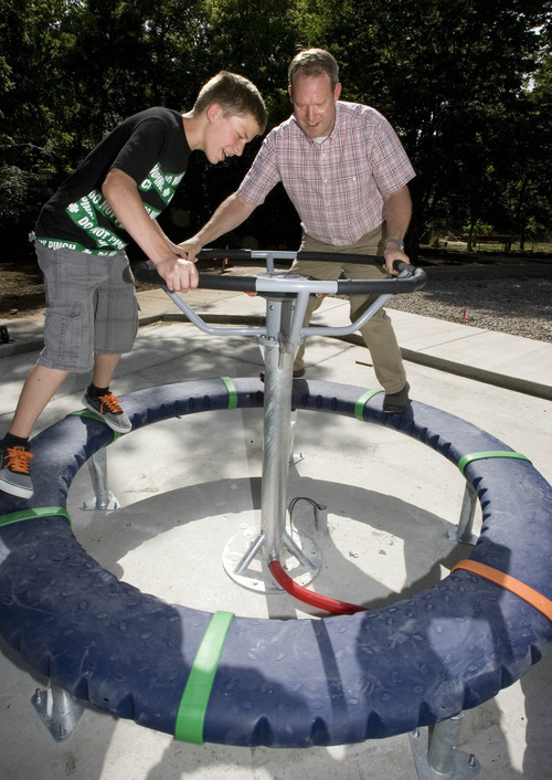 Paul Fraughton | Salt Lake Tribune Soren Selph, 12, and his father Morgan Selph, a landscape architect for Salt Lake County Parks and Recreation, play recently on a high-tech apparatus at  Evergreen Park.
