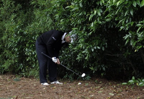 Mike Weir, of Canada, hits from the bushes off the sixth fairway during the second round the Masters golf tournament Friday, April 6, 2012, in Augusta, Ga. (AP Photo/David J. Phillip)