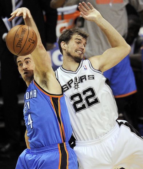 Oklahoma City Thunder power forward Nick Collison (4) and San Antonio Spurs center Tiago Splitter (22), of Brazil, go after a rebound during the second half of Game 1 in their NBA basketball Western Conference finals playoff series, Sunday, May 27, 2012, in San Antonio. (AP Photo/Darren Abate)