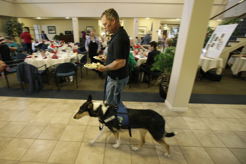 U.S. Army Spc. Mike Ballard walks with Apollo, his service dog, as he gets ready to eat lunch before speaking at an assisted living facility in DuPont, Wash., Friday, May 17, 2012. Ballard says his dog helps him get through the worst symptoms of the post-traumatic stress disorder that is a remnant of an explosion in Afghanistan that ended his career as an Army medic. (AP Photo/Ted S. Warren)