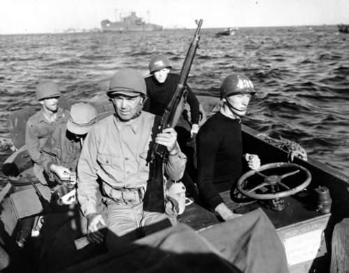 Commander Jack Dempsey, holding rifle, rides a Coast Guard landing craft to the Okinawa Beach in the Philippines a few hours after the initial attack began on the Japanese Ryuku Island in April, 1945 during World War II.  The former heavyweight champion is an officer in the U.S. Coast Guard.  (AP Photo)