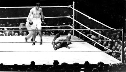 Heavyweight champion Jack Dempsey stands over challenger Luis Firpo down on the canvas in the second round of their title bout at the Polo Grounds in New York City on Sept. 14, 1923.  Referee Gallagher begins the full count of ten over the