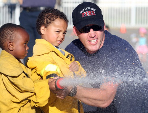 Rick Egan  | The Salt Lake Tribune   Two-year-olds, Archie Bikuspie and Lucas Upchurch, use a firehouse with the help of Salt Lake firefighter, Derek Mickelson, during the safety fair at Fire Station #7, near the Utah State Fairgrounds, Friday, June 1, 2012.