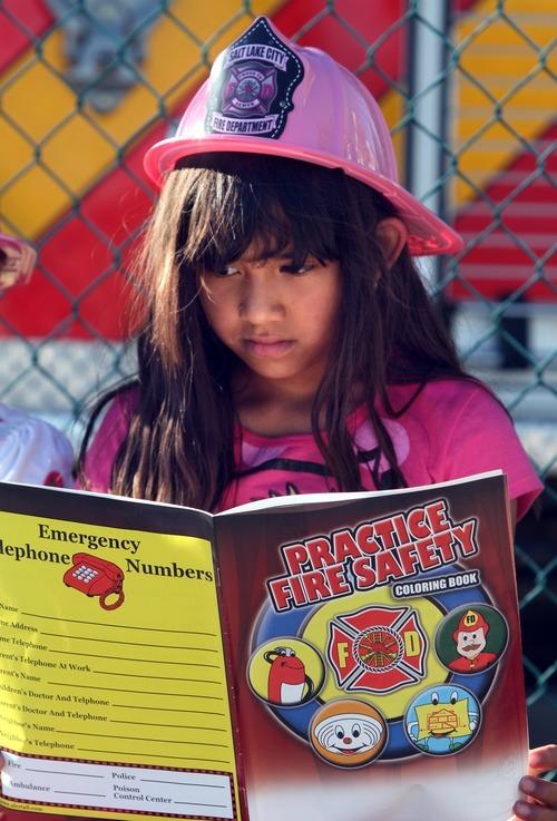 Rick Egan  | The Salt Lake Tribune   Eight-year-old Jasmine Corenja,reads books on fire safety at the safety fair at Fire Station #7, near the Utah State Fairgrounds, Friday, June 1, 2012.