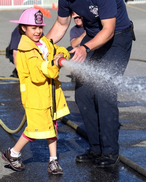 Rick Egan  | The Salt Lake Tribune   Seven-year-old Ashley Corenja, sprays water during the Firefighter Combat Challenge for the kids at the safety fair at Fire Station #7, near the Utah State Fairgrounds, Friday, June 1, 2012.