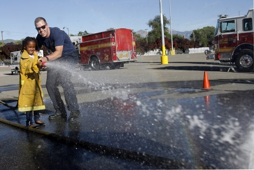 Rick Egan  | The Salt Lake Tribune   Salt Lake City fire fighter, Tristan Schroeder, helps six-year-old Hanon Osman with the fire house, during the Firefighter Combat Challenge for the kids at the safety fair at Fire Station #7, near the Utah State Fairgrounds, Friday, June 1, 2012.