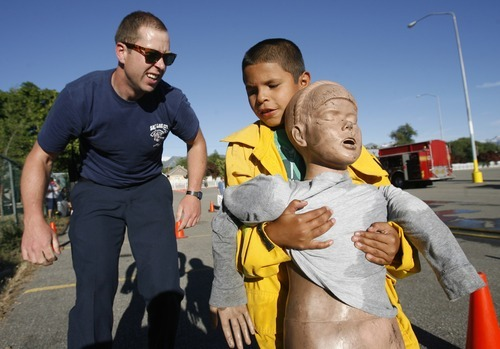 Rick Egan  | The Salt Lake Tribune   Salt Lake City fire fighter, Tristan Schroeder, helps Juan Carlos, 10, as he drags a dummy to safety, during the Firefighter Combat Challenge for the kids at the safety fair at Fire Station #7, near the Utah State Fairgrounds, Friday, June 1, 2012.