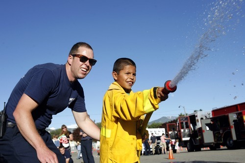 Rick Egan  | The Salt Lake Tribune   Salt Lake City fire fighter, Tristan Schroeder, assits Juan Carlos, 10, with the fire house, during the Firefighter Combat Challenge for the kids at the safety fair at Fire Station #7, near the Utah State Fairgrounds, Friday, June 1, 2012.