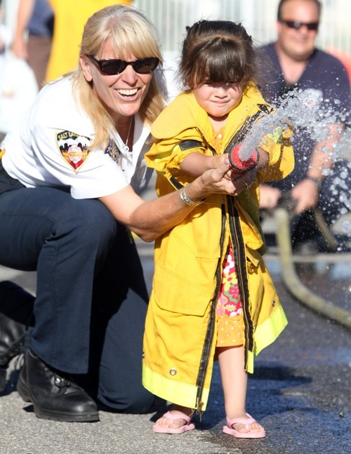 Rick Egan  | The Salt Lake Tribune   Fire Chief Martha Ellis, helps Kayla Al-Hamad, 3, with the fire house, during the Firefighter Combat Challenge for the kids at the safety fair at Fire Station #7, near the Utah State Fairgrounds, Friday, June 1, 2012.