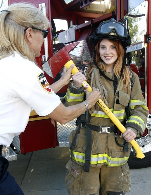Rick Egan  | The Salt Lake Tribune   Fire Chief Martha Ellis, hands Mia Chase an Ax, as she tries on fire fighter gear at the safety fair at Fire Station #7, near the Utah State Fairgrounds, Friday, June 1, 2012.