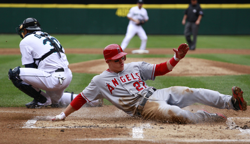 Seattle Mariners catcher Miguel Olivo, left, waits for the ball as Los Angeles Angels' Mike Trout scores in the first inning in a baseball game on Sunday, May 27, 2012, in Seattle. (AP Photo/Elaine Thompson)