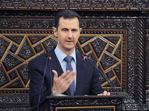 In this photo released by the Syrian official news agency SANA, shows Syrian President Bashar Assad, as he delivers a speech at the parliament in Damascus, Syria, Sunday, June 3, 2012. The president's first comments on the massacre expressed horror over the deaths of more than 100 people, nearly half of them children. U.N. investigators say there are strong suspicions that pro-government gunmen carried out the killings, but Assad denied that. (AP Photo/SANA)