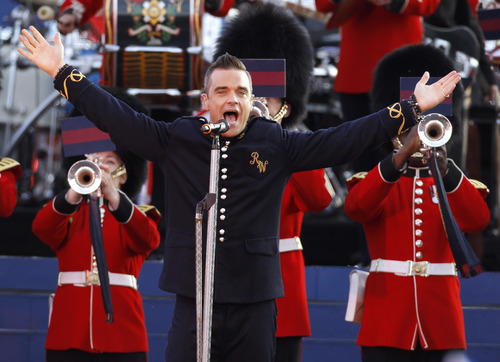 Singer Robbie Williams performs at the Queen's Jubilee Concert in front of Buckingham Palace, London, Monday, June 4, 2012. The concert is a part of four days of celebrations to mark the 60 year reign of Britain's Queen Elizabeth II. (AP Photo/Joel Ryan)
