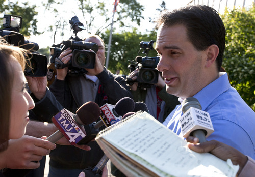 Wisconsin Republican Gov. Scott Walker talks to reporters after voting Tuesday, June 5, 2012, in Wauwatosa, Wis. Walker faces Democratic challenger Tom Barrett in a special recall election. (AP Photo/Morry Gash)
