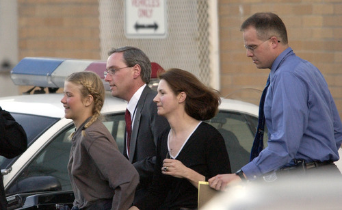 Elizabeth Smart, accompanied by her mother Lois and two unidentified men gets rushed into an unmarked van from the Salt Lake City Police department and taken to her home.  Elizabeth Smart who was abducted last June was found alive and well in Sandy early Wednesday afternoon.  Photo by Francisco Kjolseth/The Salt Lake Tribune.