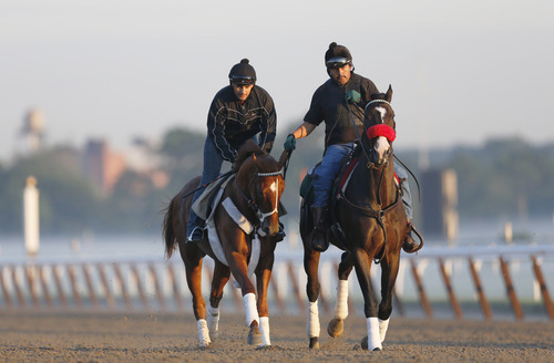 I'll Have Another, left, with exercise rider Jonny Garcia, accompanied by stablemate Lava Man, trains at Belmont Park, Friday, June 8, 2012 in Elmont, N.Y. The Triple Crown will not run Saturday in the Belmont Stakes. (AP Photo/Mark Lennihan)