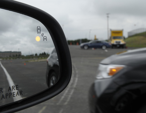 In this photo taken, Tuesday, May 22, 2012, professional test driver J.D. Ellis of Cincinnati, Ohio, demonstrates the side mirror warning signal in a Ford Taurus at an automobile testing area in Oxon Hill, Md. The display at a recent transportation conference was a peek into the future of automotive safety: cars that to talk to each other and warn drivers of impending collisions. Later this summer, the government is launching a yearlong, real-world test involving nearly 3,000 cars, trucks and buses using volunteer drivers in Ann Arbor, Mich.   (AP Photo/Susan Walsh)