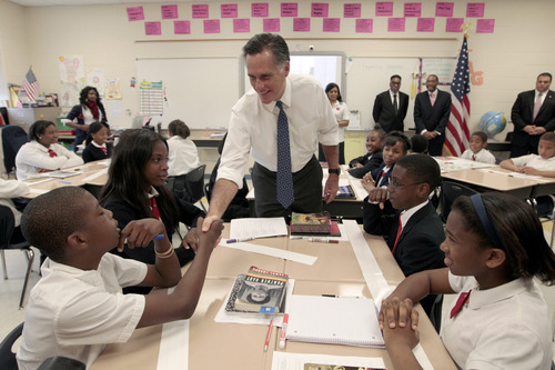 Republican presidential candidate Mitt Romney greets Justic Green during a tour of the sixth-grade language arts class at the Universal Bluford Charter School, Thursday, May 24, 2012, in Philadelphia. Romney's presence on the ballot offers voters a historic choice: a black incumbent or a white Mormon. (AP Photo/Mary Altaffer)