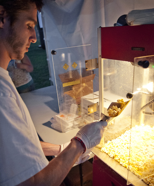 Michael Mangum     Special to the Tribune  Connor Wagner, of Salt Lake City, serves popcorn to moviegoers at Salt Lake City's Friday Night Flicks in Liberty Park on Friday, June 1, 2012.