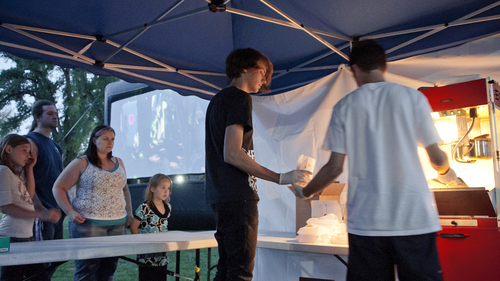 Michael Mangum     Special to the Tribune  Connor Wagner, of Salt Lake City, right, and Drew Olguin, of Ogden, center, serve popcorn to moviegoers at Salt Lake City's Friday Night Flicks in Liberty Park on Friday, June 1, 2012.