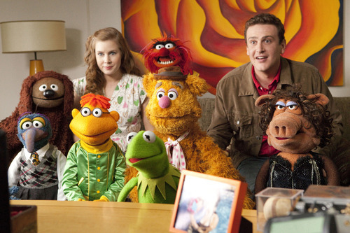 In this film publicity image released by Disney, Amy Adams, left, and Jason Segel are shown with the muppet characters in a scene from