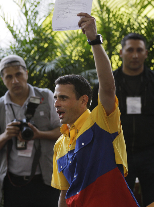 Opposition presidential candidate Henrique Capriles holds up a registration certificate at the headquarters of the National Elections Council in Caracas, Venezuela, Sunday, June 10, 2012. Capriles registered his candidacy for the presidency and will face Venezuela's President Hugo Chavez in the presidential elections scheduled for Oct. 7. (AP Photo/Ariana Cubillos)