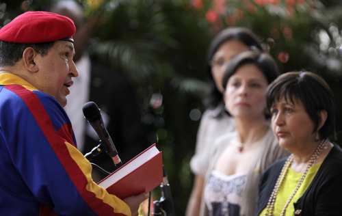 Venezuela's President Hugo Chavez, left, delivers a speech as National Electoral Council President Tibisay Lucena, right, looks at him during a ceremony to register his candidacy for the presidency at the headquarters of the National Elections Council in Caracas, Venezuela, Monday, June 11, 2012. Chavez rallied thousands of his supporters Monday, wearing his signature red beret and singing a folk song as he formalized his presidential candidacy and launched his re-election bid.  (AP Photo/Fernando Llano)