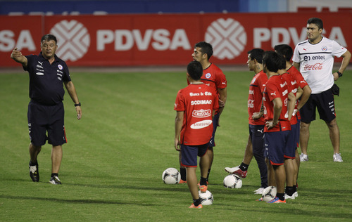 Chile's coach Claudio Borghi, left, gives instructions to his players during a training session in Puerto La Cruz, Venezuela, Friday, June 8, 2012. Chile will face Venezuela in a World Cup 2014 qualifying soccer match on Saturday. (AP Photo/Fernando Llano)