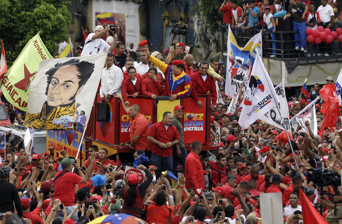Venezuela's President Hugo Chavez waves to the crowd while riding atop a truck upon his arrival to the elections office in Caracas, Venezuela, Monday, June 11, 2012. Chavez rallied thousands of his supporters wearing his signature red beret and blowing kisses to the crowd as he formalized his presidential candidacy and launched his re-election bid. (AP Photo/Ariana Cubillos)