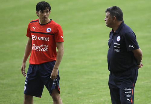 Chile's coach Claudio Borghi, right, leads his team in a training session as player Matias Fernandez walks by in Puerto La Cruz, Venezuela, Friday, June 8, 2012.  Chile will face Venezuela in a World Cup 2014 qualifying soccer match on Saturday. (AP Photo/Fernando Llano)