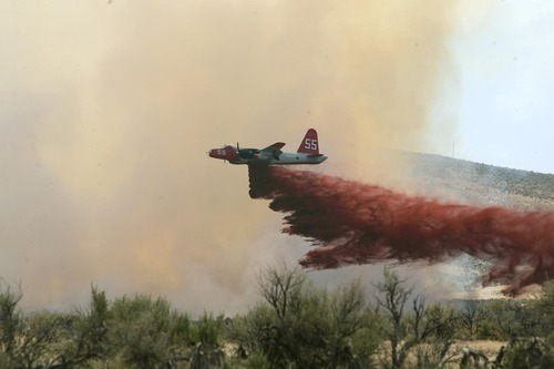 In this file photo from July 13, 2006, a P2-V Neptune air tanker drops retardant on a wildfire southwest of Elko, Nev. An air tanker dropping retardant on a remote wildfire along the Utah-Nevada line crashed Sunday, June 3, 2012, killing both crew members, authorities said. The pilots were flying a P-2V air tanker that is owned by Neptune Aviation Services of Missoula, Mont. (AP Photo/Elko Daily Free Press, Ross Andreson, file)